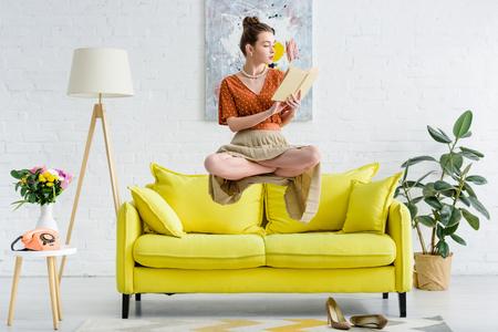 Elegante joven en posición de loto levitando en el aire mientras lee un libro en la sala de estar