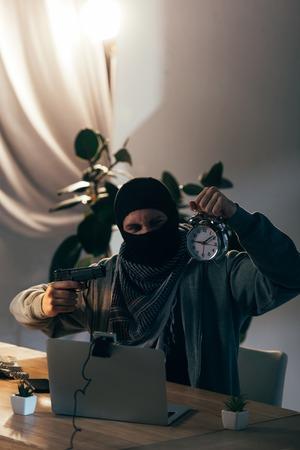 Aggressive terrorist with gun showing alarm clock in video chat Stock Photo
