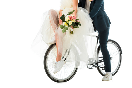 partial view of bride with wedding bouquet sitting on bicycle together with groom isolated on white Stock Photo