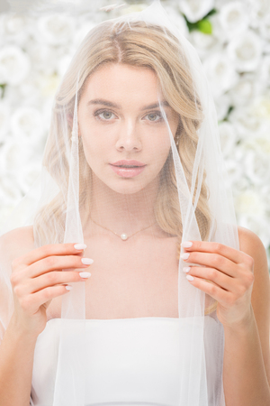 beautiful young woman with face covered with transparent bridal veil looking at camera on white floral background 스톡 콘텐츠