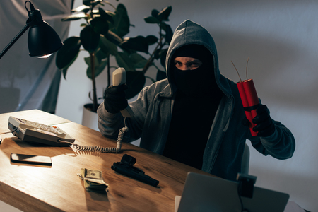Angry terrorist in mask and gloves holding handset and dynamite Stock Photo