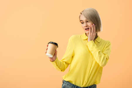 Interested young woman in yellow shirt looking at paper cup with coffee isolated on orange