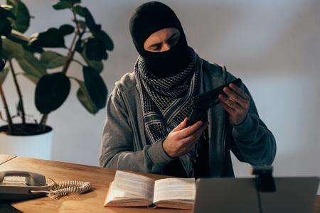 Pensive terrorist in black mask looking at gun in room