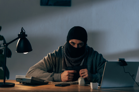 Aggressive terrorist sitting at table with gun and looking at camera Stock Photo