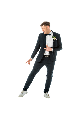cheerful groom dancing in black suit and white sneakers isolated on white