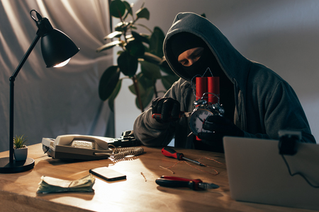 Criminal in mask sitting at table with laptop and making bomb Stock Photo