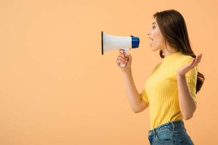 Side view of pretty brunette woman screaming in loudspeaker isolated on orange