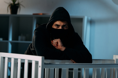 Worried kidnapper in black clothes and mask standing beside crib Stock Photo