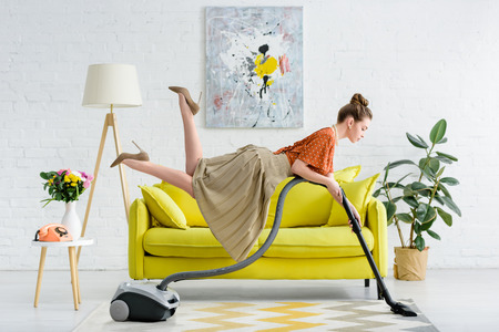 Vista lateral de la elegante joven concentrada levitando en el aire y alfombra de aspiración en el salón