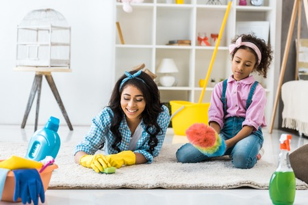 cute african american child sitting on carpet with dusting brush while mother cleaning carpet