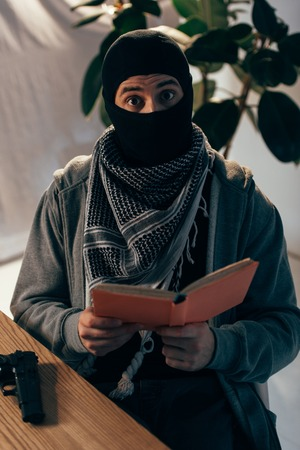 Shocked terrorist in black mask reading book at table