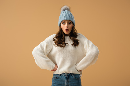 Shocked curly young woman in blue hat standing with arms akimbo isolated on beige