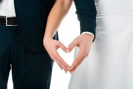 cropped view of bride and groom showing heart sign with hands isolated on white