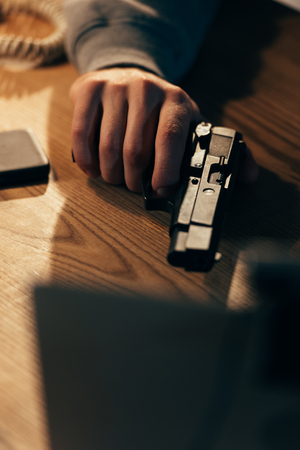 Cropped view of criminal holding gun on wooden table