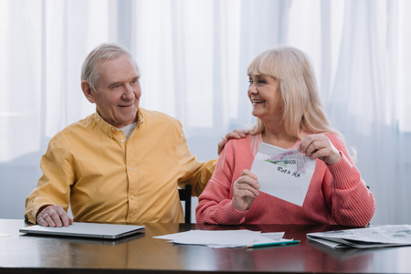senior couple holding envelope with roth ira lettering and money while sitting at table