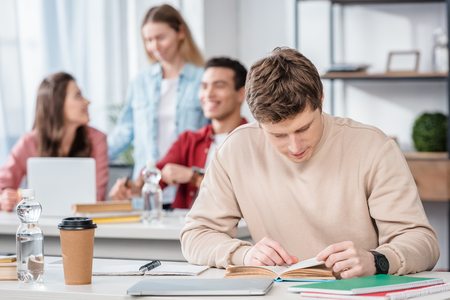 Concentrated student sitting at desk and reading book in classroom