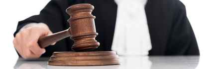 Panoramic shot of judge in judicial robe holding gavel isolated on white