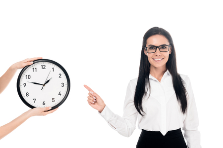 Lächelnde Geschäftsfrau mit Brille zeigt mit dem Finger auf die Uhr isoliert auf weiß Standard-Bild