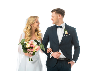 smiling bride with wedding bouquet, and happy groom in black suit looking at each other isolated on white Stock Photo - 120052294