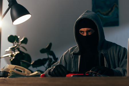 Pensive terrorist in mask and leather gloves sitting at table with telephone