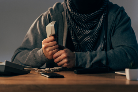 Partial view of terrorist in keffiyeh scarf holding telephone handset Stock Photo