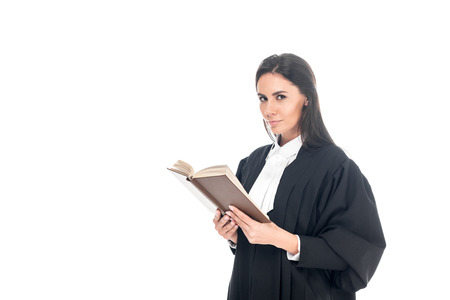 Judge in judicial robe reading book isolated on white