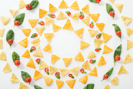 flat lay with tasty nachos and sliced chili peppers with basil and cherry tomatoes on white background