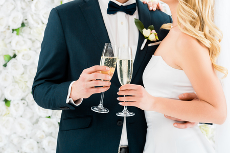 cropped view of groom and bride holding glasses of champagne on white floral background Stock Photo