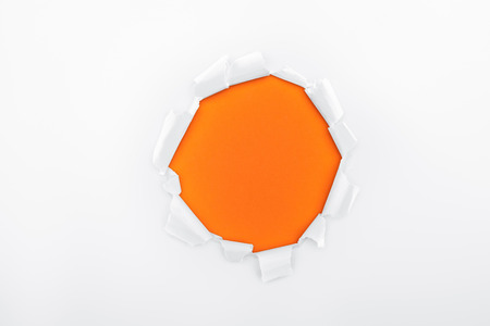 torn hole in white textured paper on orange background Stock Photo