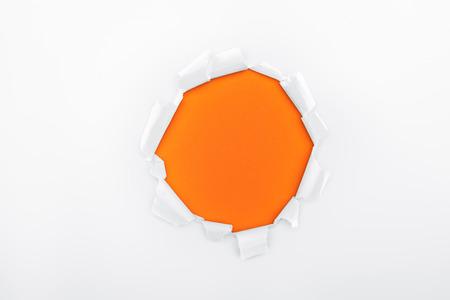 torn hole in white textured paper on orange background Reklamní fotografie