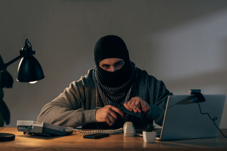 Terrorist in black mask sitting at table and loading gun