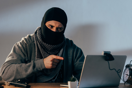 Terrorist in mask looking at webcam and pointing with finger at laptop screen