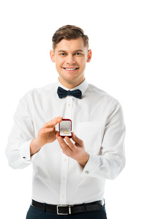 happy groom demonstrating gift box with wedding ring and looking at camera isolated on white