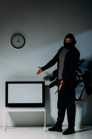Surprised thief in black mask pointing with hands at flat-screen tv with blank screen