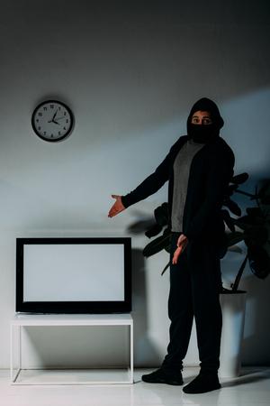 Voleur surpris en masque noir pointant les mains sur une télévision à écran plat avec écran vide
