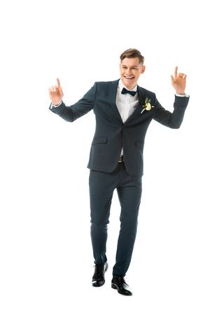 cheerful dancing groom in black suit isolated on white Stock Photo - 120052851