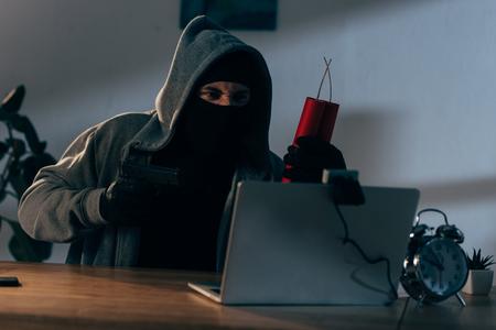 Aggressive terrorist in mask aiming gun at webcam in dark room