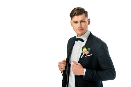 serious handsome bridegroom in bowtie and jacket with boutonniere looking at camera isolated on white Stock Photo