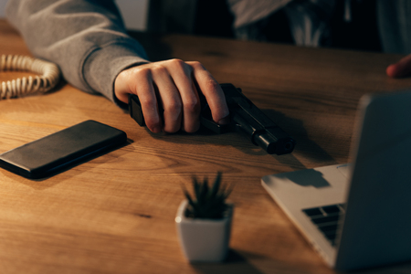 Partial view of criminal with gun and smartphone on wooden table