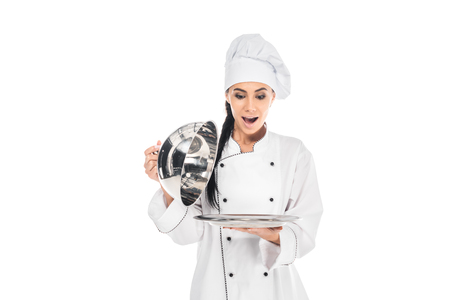 Shocked chef in hat holding tray with cloche isolated on white Zdjęcie Seryjne