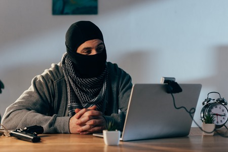 Terrorist in mask sitting with interlaced fingers and looking at webcam