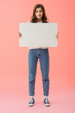 full length view of beautiful and sad woman holding empty board with copy space isolated on pink