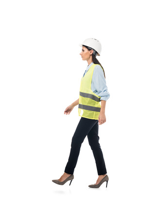 Side view of engineer in safety vest and high-heeled shoes walking isolated on white