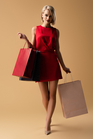 Full length view of beautiful young woman in red dress holding shopping bags
