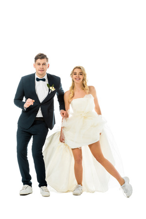 happy groom and bride in elegant clothes and sneakers dancing while looking at camera isolated on white