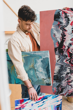 selective focus of artist holding multicolored abstract paintings
