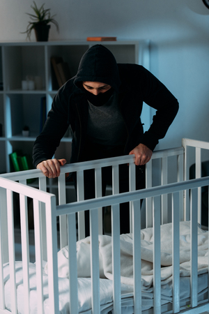 Criminal in mask standing near crib and looking at baby Zdjęcie Seryjne