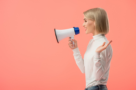 cheerful blonde woman speaking in megaphone isolated on pink