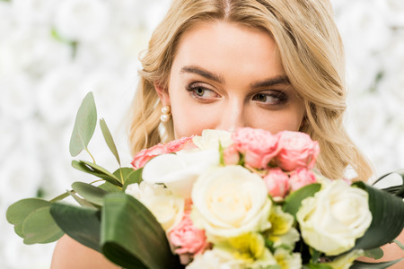 selective focus of pretty young bride enjoying flavor of wedding bouquet on white floral background