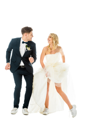 happy groom and bride dancing in elegant clothes and sneakers while looking at each other isolated on white